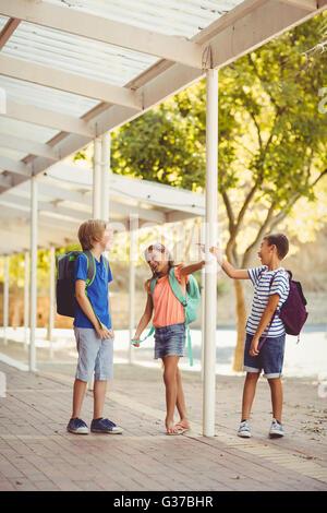 School kids talking to each other in school corridor - Stock Photo
