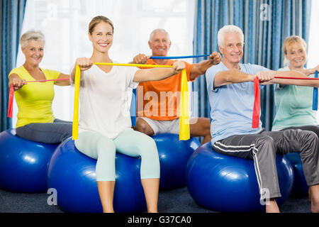 Seniors using exercise ball and stretching bands - Stock Photo