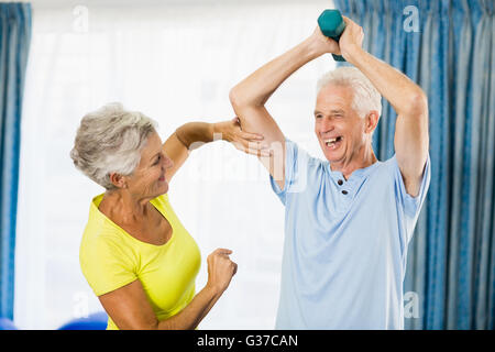 Senior woman feeling muscles of man - Stock Photo
