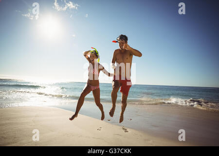 Couple wearing diving mask jumping on beach - Stock Photo