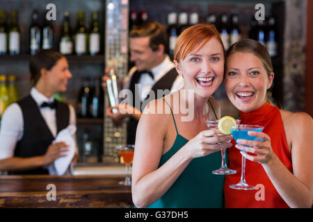 Portrait of friends holding a cocktail in front of bar counter - Stock Photo