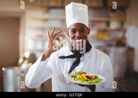 Portrait of happy chef making ok sign - Stock Photo