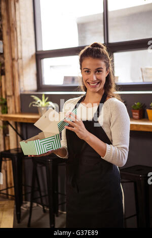 Waitress holding boxes with a cake inside - Stock Photo