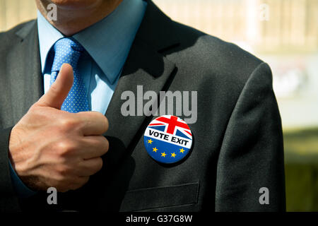 British businessman giving a thumbs up and wearing a VOTE EXIT pin badge, in support for leaving the European Union. - Stock Photo