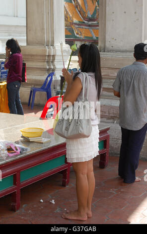 A young Thai woman prays to buddah whilst holding incense sticks in her hands at the local temple - Stock Photo