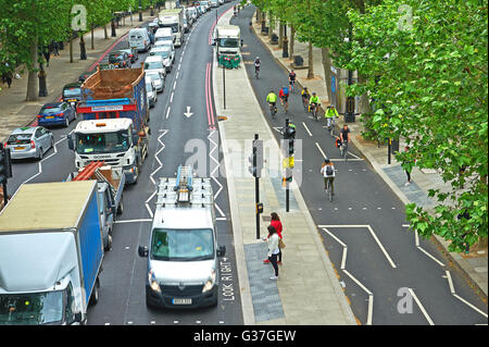 Traffic queuing on Victoria Embankment in Central London whilst commuters cycle past on the new two way cycle track - Stock Photo