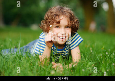 The boy of 8-9 years lies in a dense green grass. The boy has curly hair, a turned-up nose, chubby lips and blue - Stock Photo