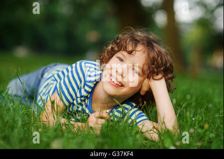 The boy lies in a green grass, having propped up the head a hand. He looks in a camera and smiles. The boy has curly - Stock Photo