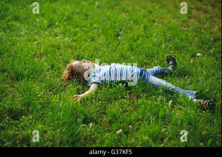 The boy lies in a dense green grass on a lawn. He lies on a back, having widely stretched hands and legs. - Stock Photo