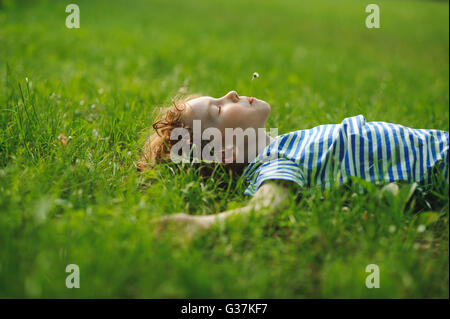 The boy of 8-9 years lies on a back in a dense green grass. He has stretched hands in the parties and has closed - Stock Photo