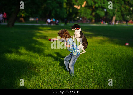 The boy trains a dog.In a summer garden the boy of 8-9 years plays with a dog.In a hand at the boy a disk.Highly - Stock Photo