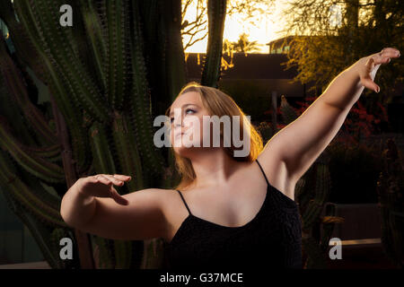 A beautiful, blond dancer poses in front of cacti at sunset.  Her face is turned to the light and she is lovely. - Stock Photo