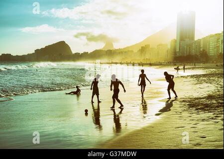 RIO DE JANEIRO - OCTOBER 30, 2015: Silhouettes of Brazilians play altinho beach football in a circle on Copacabana - Stock Photo
