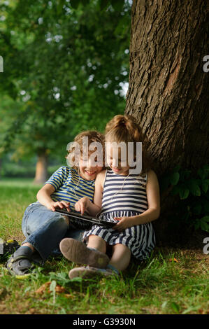 Brother and sister of 8-9 years play with passion on the tablet. Children are very keen. They with interesy look - Stock Photo