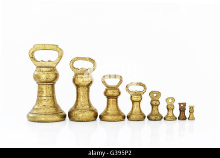 Old fashioned Imperial brass weights which were used on traditional scales,ranging from 4Lbs down to 1oz, pre metric. - Stock Photo
