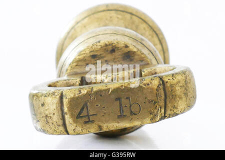 4 lb old fashioned Imperial brass weight which was used on traditional scales, pre metric. - Stock Photo