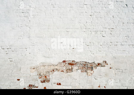 white brick wall fragment with damaged paint part - Stock Photo