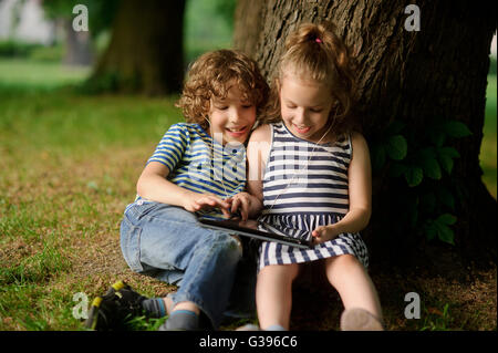 The brother and the sister of 8-9 years play with passion on the tablet. They sit having leaned against a trunk - Stock Photo
