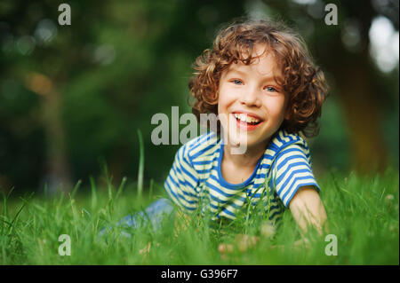 The cheerful boy lies in a dense green grass. He has blond curly hair, a turned-up nose and blue eyes. Playful and - Stock Photo