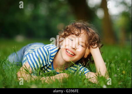 The boy lies on a green lawn in park, having propped up the head a hand. He looks in a camera and smiles. The boy - Stock Photo