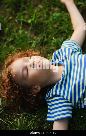 The boy lies on the earth having stretched hands in the parties. Eyes are closed from pleasure. Blond curly hair. - Stock Photo