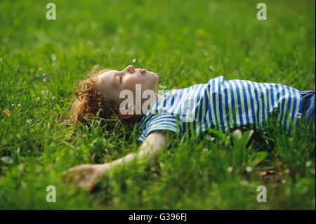 The little boy lies in the field on a green grass. He has stretched hands in the parties. In a mouth a floret. Eyes - Stock Photo