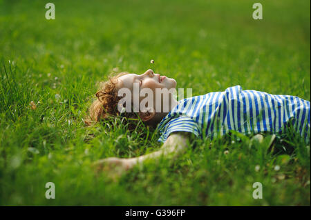 The boy of 8-9 years lies in the field on a green grass. He has stretched hands in the parties. In a mouth a floret. - Stock Photo