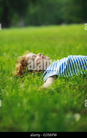 The little boy lies on a green lawn in park. He has stretched hands in the parties. In a mouth a floret. Eyes pensively - Stock Photo