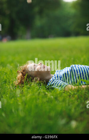 The boy of 8-9 years lies on a green lawn in park. Eyes are closed from pleasure. Blond curly hair. On cheeks a - Stock Photo