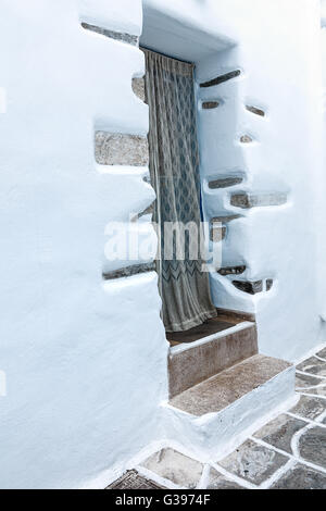 An entrance to a small white-washed house on typical street in Mykonos - Stock Photo