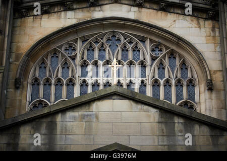 Detail on the exterior of Manchester Cathedral   A gold coloured cross framed by an stone window Church religion - Stock Photo