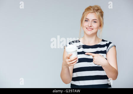 Cheerful pretty young woman pointing on cup for coffe to go over white background - Stock Photo