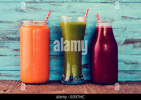 closeup of three different fresh smoothies served in a glass, a glass jar and a glass bottle with red drinking straws - Stock Photo