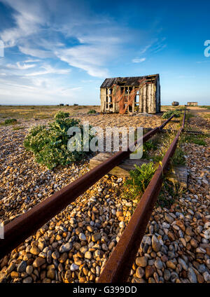 An old fishing hut and tracks on the shingle beach of Dungeness, Kent. - Stock Photo