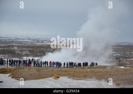 Tourists waiting for a new eruption of the Strokkur geyser, a station of the famous Golden Circle of Iceland. - Stock Photo