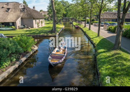 Giethoorn, Netherlands. Electric boat in the Dorpsgracht or Village Canal with romantic young Chinese couple in - Stock Photo