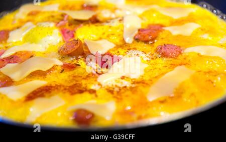 Frying ham and eggs with cheese, sausages and pepper in pan sprinkled by caraway seeds closeup. - Stock Photo