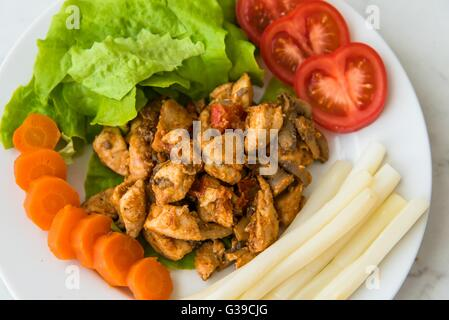 Fried chicken meat served on plate with white asparagus, carrot, tomato and lettuce. Top view - Stock Photo