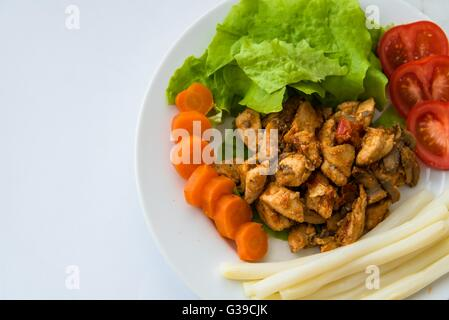 Fried chicken meat served on plate with white asparagus, carrot, tomato and lettuce. Top view. Space on left side. - Stock Photo