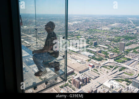A man has his photograph taken on the glass balcony to the observation deck of the Willis Tower, with an aerial - Stock Photo
