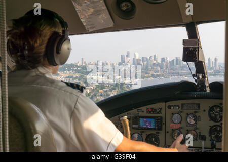 Female pilot of float plane coming in to land on Lake Union, Seattle with the city skyline seen through the cockpit - Stock Photo