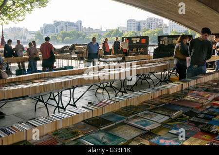 Locals and tourists browsing through the books at the Southbank book market under Waterloo Bridge, London. - Stock Photo