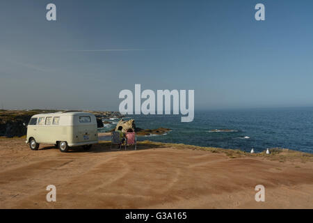 Portugal, Alentejo, Porto Covo old-timer VW camper van with couple sitting outside - Stock Photo