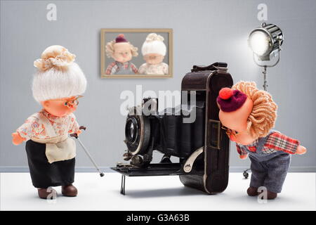 Puppets of senior photographer taking, with passion until the end, pictures of his old ladies with vintage camera - Stock Photo
