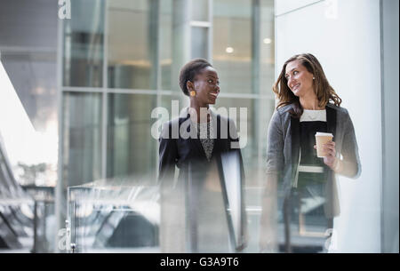 Corporate businesswomen with coffee talking and walking - Stock Photo
