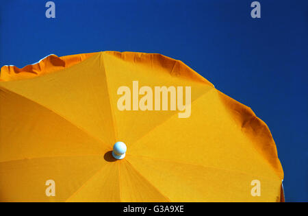 Bright yellow sunshade and deep blue sky: Gruissan Plage, Aude, Occitanie, France - Stock Photo