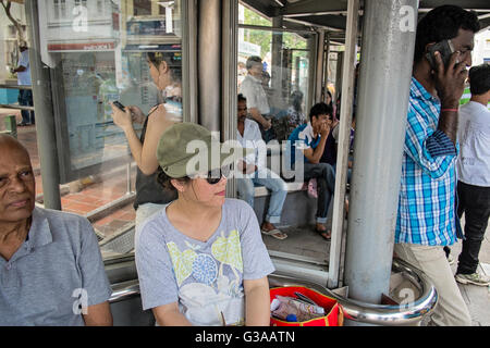 Commuters wait at a bus stop on Serangoon Road in Little India, Singapore - Stock Photo