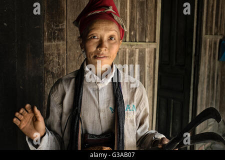 A young Red Dao woman holds the scythes she uses for farming in the village of Ban Knoang, Sapa, Lao Cai Province, - Stock Photo
