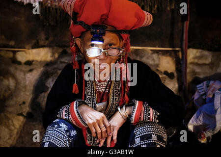 A middle aged Red Dao woman sells tribal handicrafts at a night street market in Sapa, Lao Cai Province, Vietnam - Stock Photo