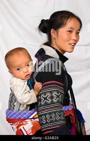 A Hmong woman and baby, wearing traditional costume in Sapa, Lao Cai Province, Vietnam - Stock Photo